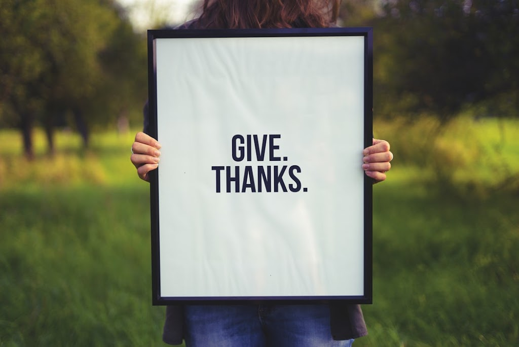 Give thanks frame is held by a woman in a field on Mariedeveaux.com thanksgiveaway promo page for free 90 minute coaching sessions.