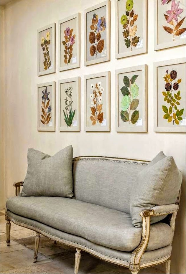 Vividly colorful framed botanicals hung above a French settee in an elegant home in Houston with interiors designed by Pamela Pierce.