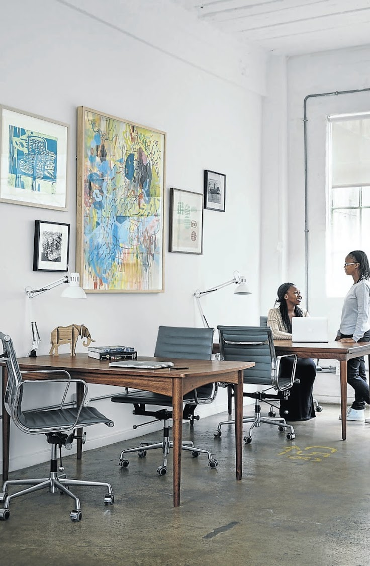 A gallery wall and the post-modern tables which double as desks give the work area a homey feel.