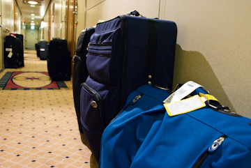 Luggage left in the hallway outside stateroom doors.