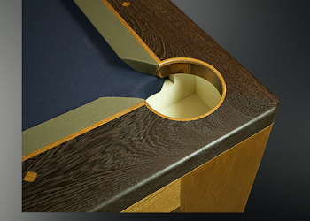 Corner pocket of a pool table with dark wood and dark blue felt