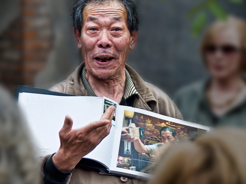 Photo: Mr. Lee, famous Cricket Wrangler (retired), shows his scrapbook of Photos and clippings. - Beijing, April 2009