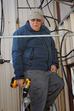 Photo: Ted, VE4VID, installing the support brackets for the coax along the wall on the roof