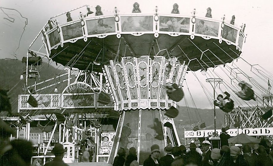 Acrobats whirling to the sound of a barrel organ on a chain carousel at the National Fair, Bergen, Norway, 1928.