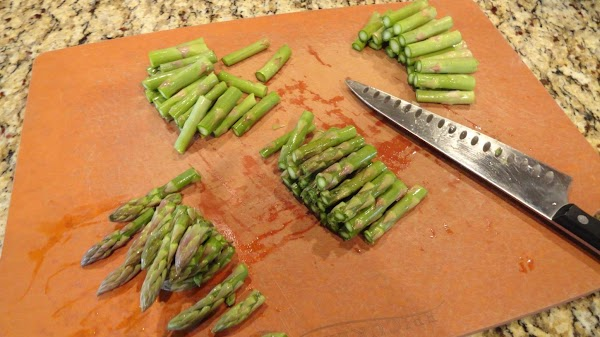 Cutting asparagus into 1 inch pieces.