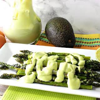 Creamy Avocado Hollandaise Sauce Over Oven Roasted Asparagus.
