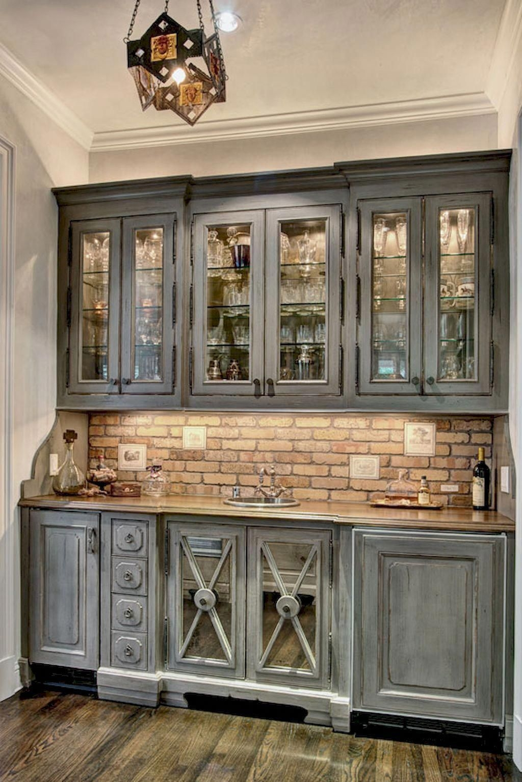 grey distressed weathered kitchen cabinets with glass doors brick backsplash and antique vintage decor