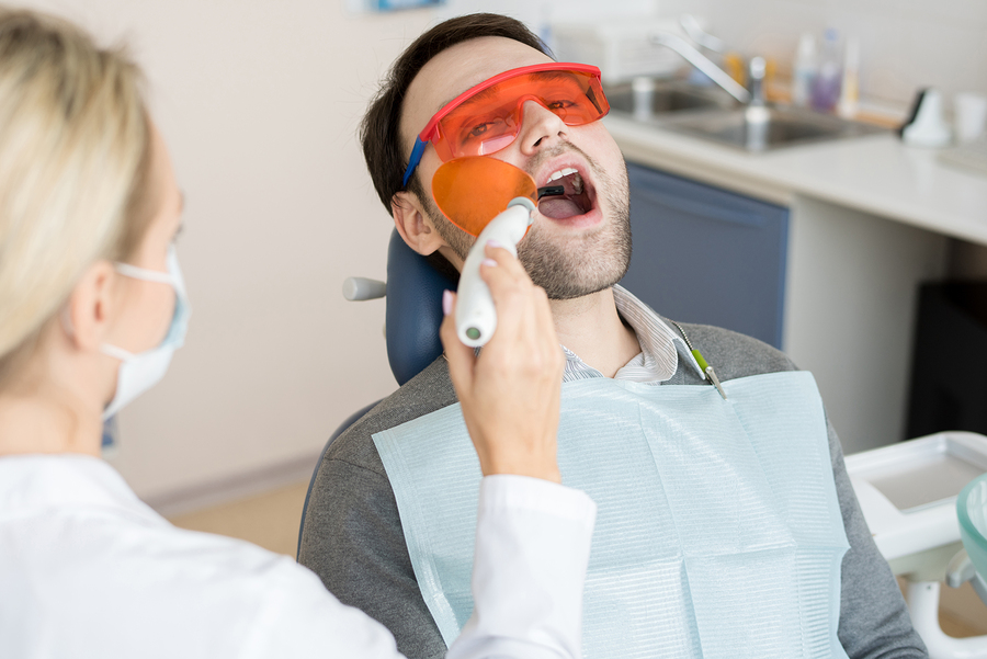 Young man receiving laser dental treatment at his dentist wearing protective glasses