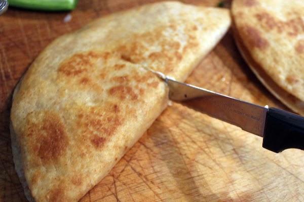 Quesadilla being cut in half.
