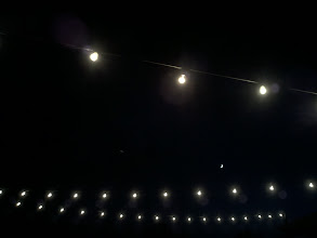 Photo: Took a break from dancing at a wedding reception, and found the Cheshire cat in the sky smiling at us through the lights.