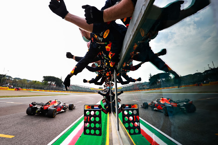 Race winner Max Verstappen of the Netherlands driving the (33) Red Bull Racing RB16B Honda passes his team celebrating on the pitwall during the F1 Grand Prix of Emilia Romagna at Autodromo Enzo e Dino Ferrari on April 18, 2021 in Imola, Italy.