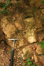 Photo: A kalapács mögött a középső- és felső-jura korú Dorogói Mészmárga Formáció rétegei húzódnak