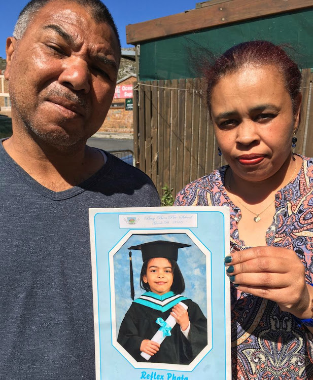 Emaan Solomons's grandparents Ronald Solomons and Pearl Daniels hold her portrait on the spot where she was killed on Tuesday.