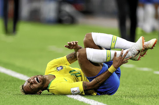 Neymar screams in pain after being fouled. The writer says his antics are so popular kids are now encouraged to roll on the ground during play to feign injury.