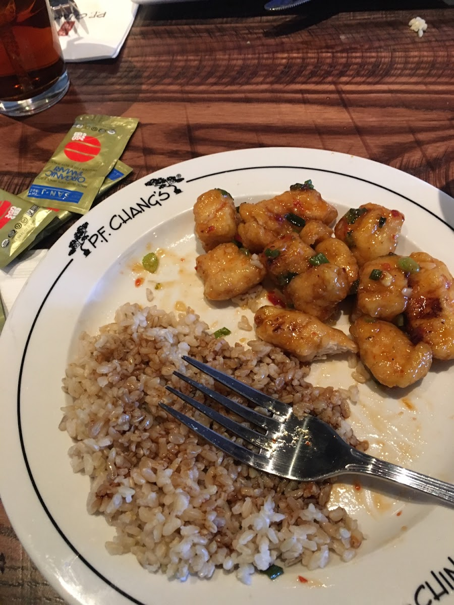 Chang's Spicy Chicken with a side of brown rice and gluten free soy sauce. Served on a marked plate to indicate gluten free.