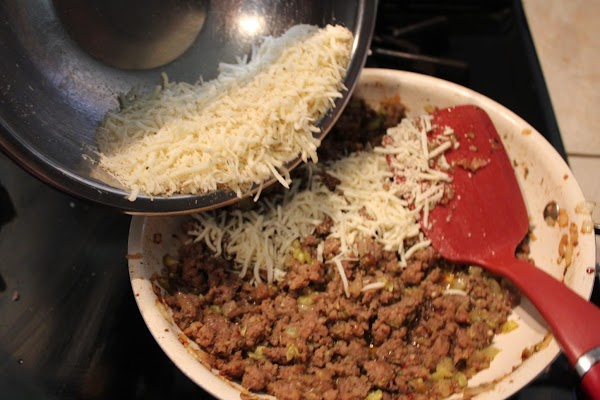 Into the sausage mixture stir in the cheeses and bread crumbs. Whisk the egg...