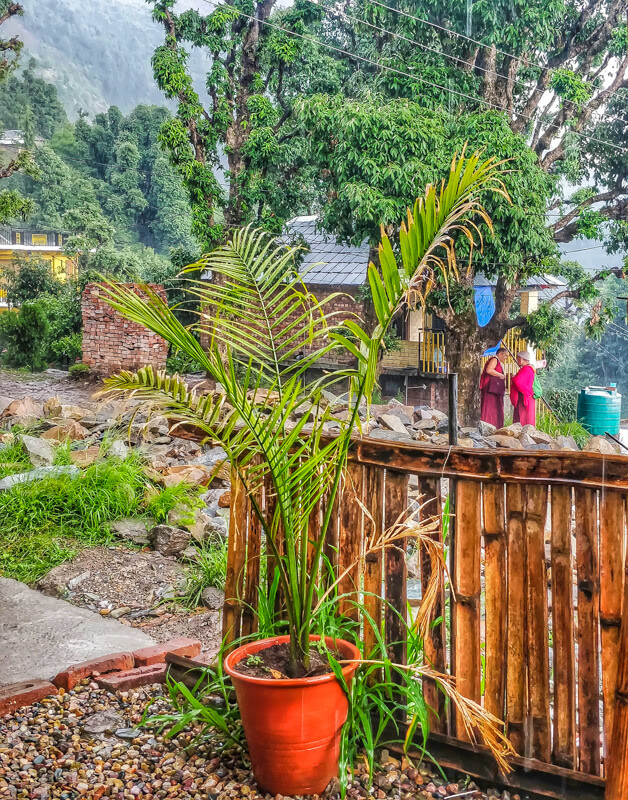 monks+standing+in+shade+bhagsu+village+himachal+pradesh