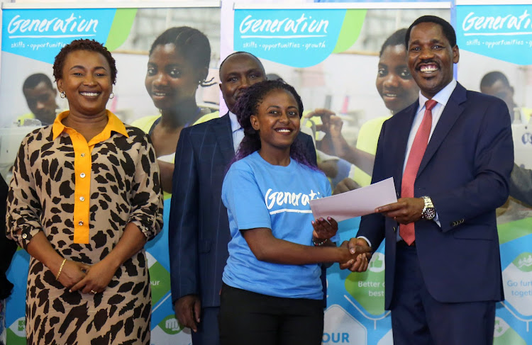 Trade CS Peter Munya (right) presents a certificate to Mercy Musembi during the 7th Generation Kenya graduation ceremony held at KICC, Nairobi. Looking on is Sylvia Mulinge, Safaricom Foundation trustee