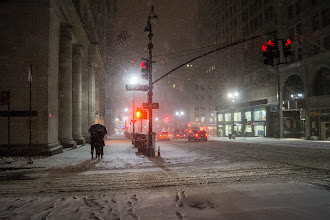 Photo: New York winter night on 5th Avenue  This is one of my favorite scenes from last Friday night's snowstorm with the Sony A99. Quite a few people asked me how I was able to take photos without having snow and water droplets on my camera lens. It was quite a production actually. As I explained in my initial post, I wrapped my camera lens in plastic and then poked a hole in a plastic bag and threaded the lens through that hole. The rest of the plastic bag went over the camera as a covering. I secured the plastic with a lens hood which came in handy during periods of blowing snow. When I wasn't taking a photo I would point the camera down lens to the ground so that when snow blew towards me, it would blow and collect on the outside of the lens hood keeping the lens relatively dry and clean. I also had a lens filter on the lens.   This meant that I only had a tiny amount of time to shoot each shot. I shoot in manual mode because it's a long-standing preference of mine so I already had set up the settings that worked for the majority of shots (I did have to adjust a lot once I got to the Times Square area due to the lighting there). In the event that there was a shot I wanted to go for that was in the direction of blowing snow, I would just quickly take the shot and then scurry towards an awning, scaffolding cover, or dry entrance where I would wipe the lens down with a lens wipe.   I finally got around to putting some of the more popular photos from my winter storm Nemo in NYC set that I took and shared this past weekend during the (non) blizzard in my main portfolio and store here: http://goo.gl/KzVFX . They are scattered throughout the rest of my photos. A number of people asked when I was going to put them up for sale so I have been slowly putting the photos from the set into my portfolio - store. I actually have more photos that I haven't even touched from that night that I hope to go through in the next few weeks and eventually share.   I really didn't expect 