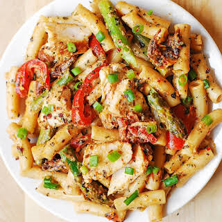 Creamy Chicken Alfredo Pasta with Bell Peppers, Asparagus, and Sun-Dried Tomatoes.