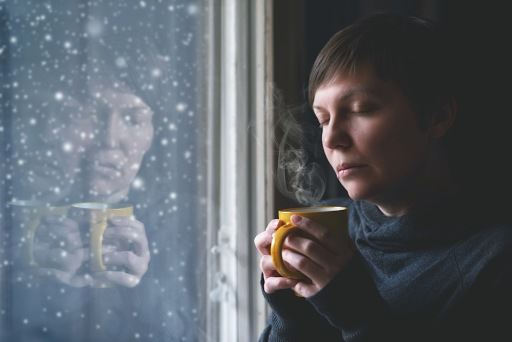 A woman holding a mug looking pensively out of a window with snow falling down.