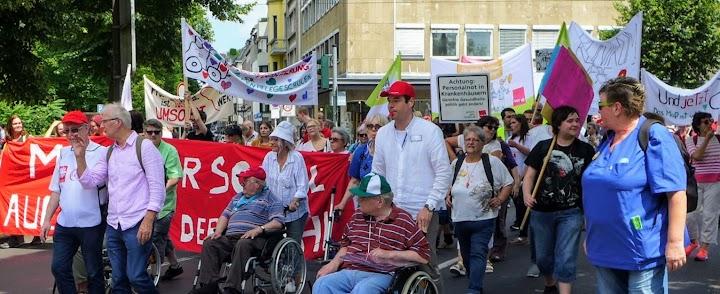 Demonstrierende Fußgänger und Rollstuhlfahrer mit Fahnen, Plakaten und Transparenten.