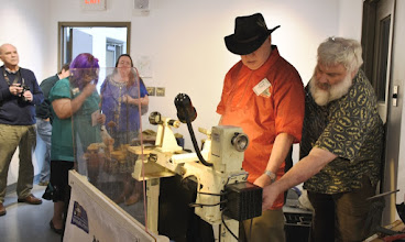 Photo: Eliot Feldman is next in line, and John shows him some details about how this lathe works.