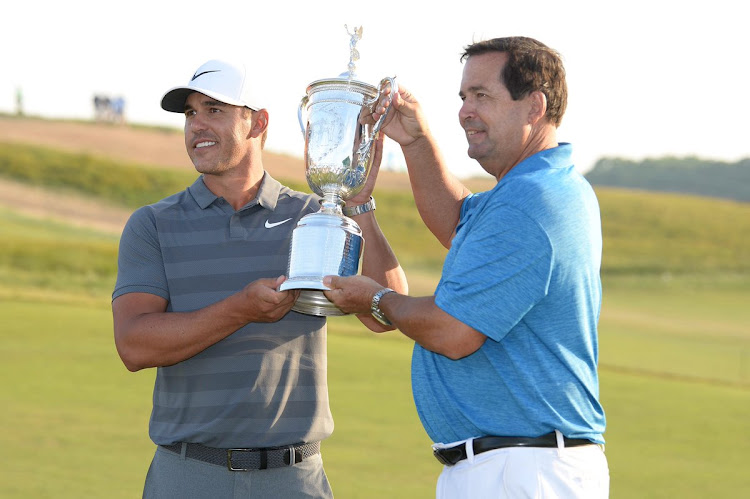 2018 US Open winner Brooks Koepka and his dad, Bob, pose for photographs.