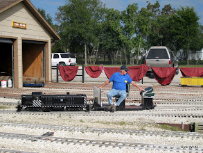 Photo: Peter Bryan making up a string of cars with the loco and car covers made by Mary Lou Schoenberg hanging up to dry on the fence.    SWLS at HALS 2009-1107