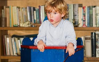 Photo: Knabe im musealen Kinderstuhl aus dem 19. Jht
