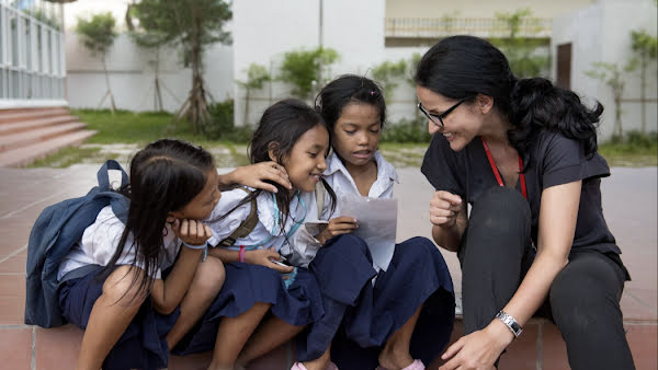 A woman smiling and sitting with three students outside