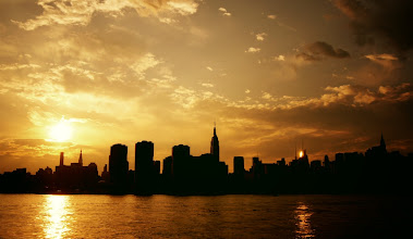 """Photo: """"Two suns...""""  Sunset over the New York City skyline. New York photography.  In the last minutes before the night rides across the sky with its trailing blanket of darkness, the sun melts over the rapidly darkening silhouettes in the distance pouring itself into the water like liquid gold.  It's in these last minutes before the city lights illuminate the urban landscape like constellations, before every last ember of daylight fades that the remains of the day extinguish themselves in the long sighs of evening wanderers.    You can view this post along with info about prints of this image if you wish at my site here:  http://nythroughthelens.com/post/11927829353/sunset-over-the-new-york-city-skyline-as-viewed    Tags: #MyTownTuesday #photography #landscape #newyork #newyorkcity #newyorkcityphotography #sunset #writing #prose #poetry #skyline #sun #city"""