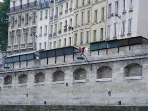 Photo: The Seine-side view of the bouquinistes, the roughly 250 booksellers on the quays whose green metal boxes are a familiar landmark in this part of the city. They first appeared here in the early 19th century (when their wares included lead figurines, which have been recovered in some number from the Seine riverbed), with their present storage boxes defined by 1993 regulations.
