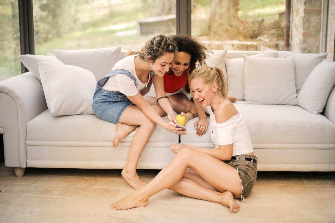 Cheerful multiracial female friends resting on sofa and floor while watching funny video on smartphone