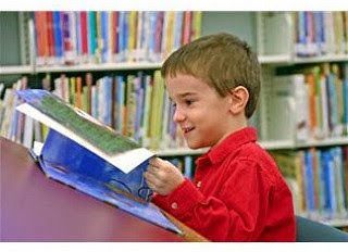 Little boy in library smiling and looking at book