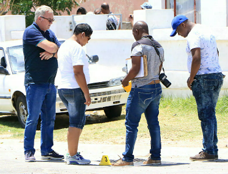 SAPS members investigate at the scene where Mbasa Dlamini, 11, was shot in Kwazakhele