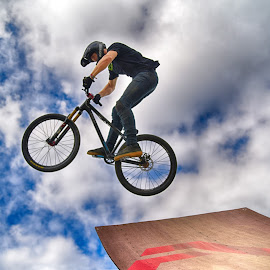 by Marco Bertamé - Sports & Fitness Other Sports ( clouds, wheel, letter, a, dow, stunt, ramp, jump, flying, two, red, sky, blue, cloudy, brown, grey, air, high )