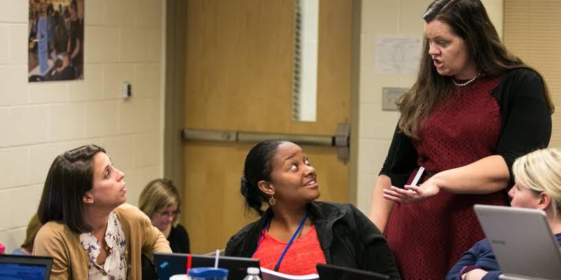 Teacher talking with fellow teachers at a training seminar