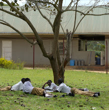 """Photo: Secondary students """"studying"""".  Clinic in the background."""