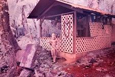jongen met knuppel, gekleed in kort broekje, staand voor een huis, waarbij alles rose-bruin gekleurd is