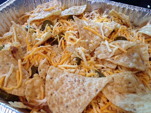 LAYER TORTILLA CHIPS ON THE BOTTOM OF A 9x13 TIN PAN NEXT SPRINKLE SOME SHREDD...