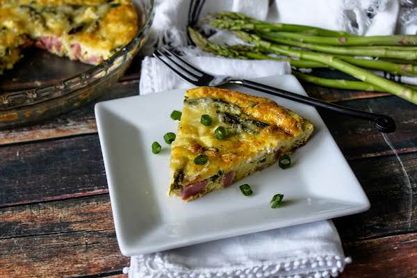 A Slice Of Baked Egg Frittata On A Plate With Scallions Sprinkled Around.