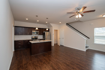 Spacious living area with wood flooring looking into kitchen