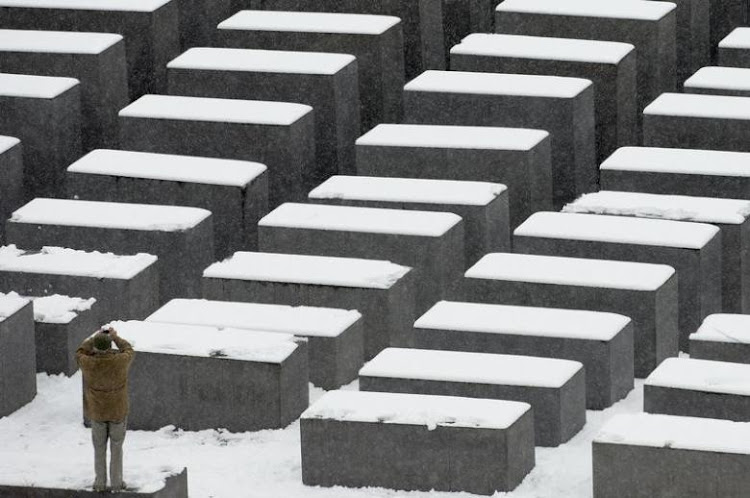 A man takes pictures of the Holocaust memorial after heavy snowfall in Berlin. Picture: REUTERS