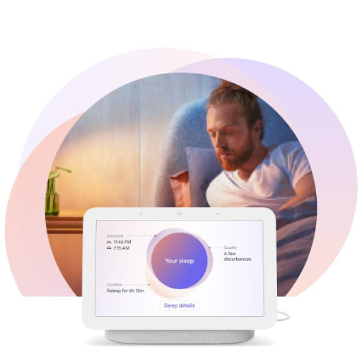 The man is sitting upright in bed and is turning toward his Nest Hub display at his bedside. It shows personalised insights about his sleep.