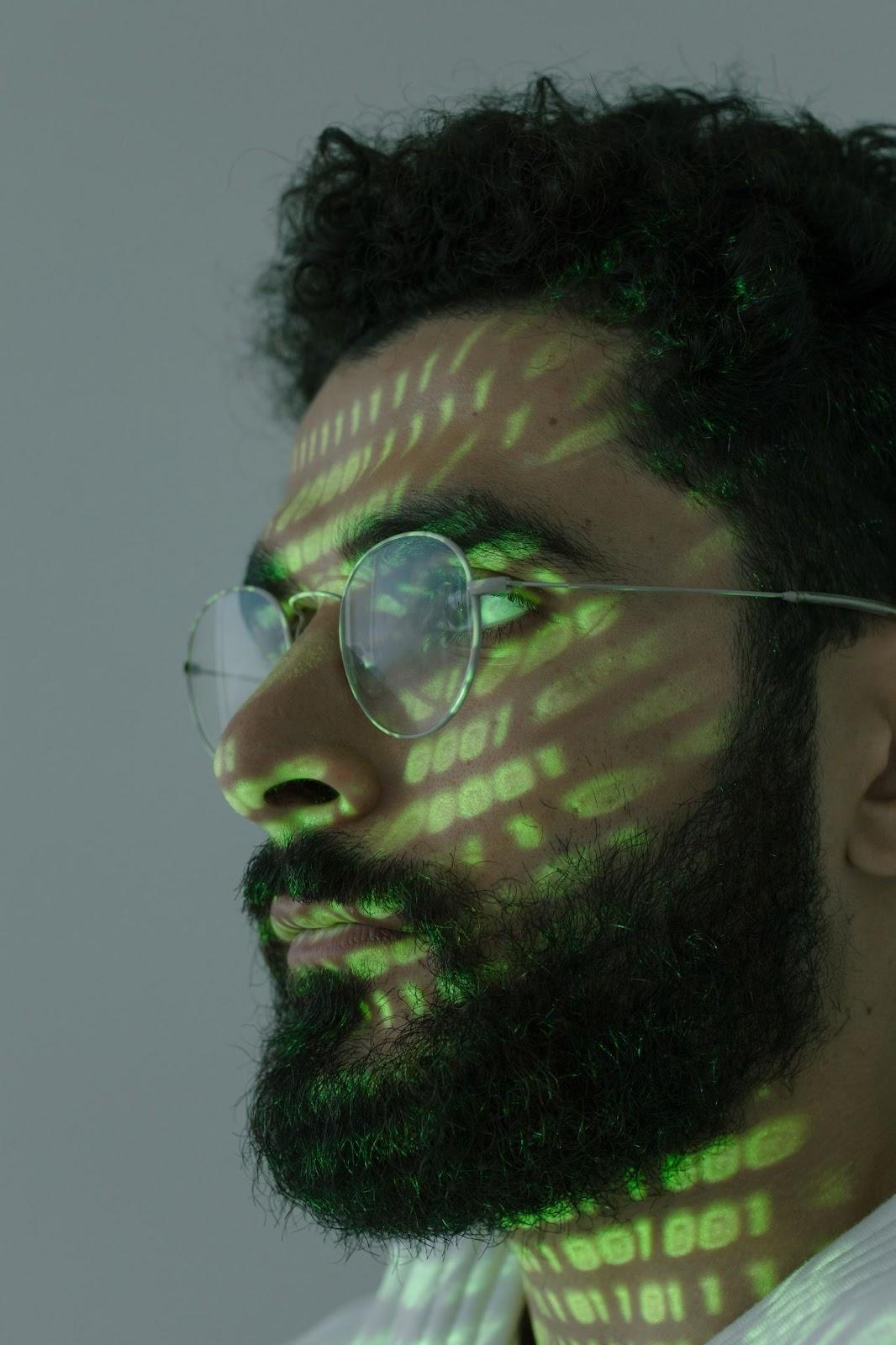 Foto de um homem olhando para o lado com luzes verde no rosto