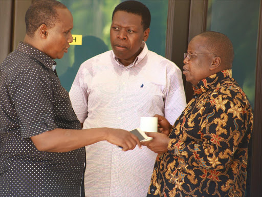 Devolution CS Eugene Wamalwa (center) chats with Chief administrative secretary Hussein Dadho (left) and outgoing devolution PS Micah Powon during a two day senate devolution induction conference at white sands hotel in Mombasa county yesterday.Photos / JOHN CHESOLI