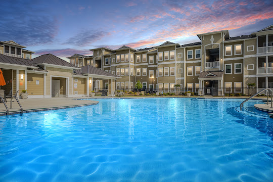 Swimming pool at dusk, with clubhouse and apartment buildings with tan siding and white trim surrounding