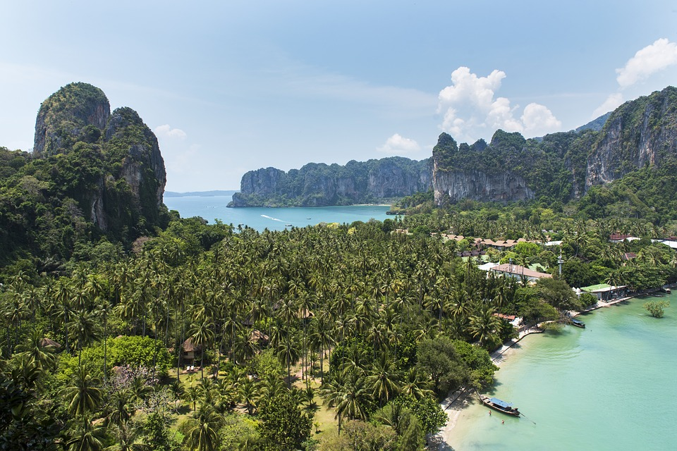 View of Railay bay, Krabi with mountains overlooking a resort surrounded by forest, with beaches.