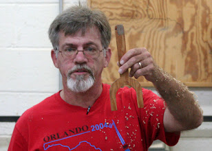 Photo: Keith makes a tenon for the jaws to grasp when he turns it around.  He shows his jig for measuring the tenon size.
